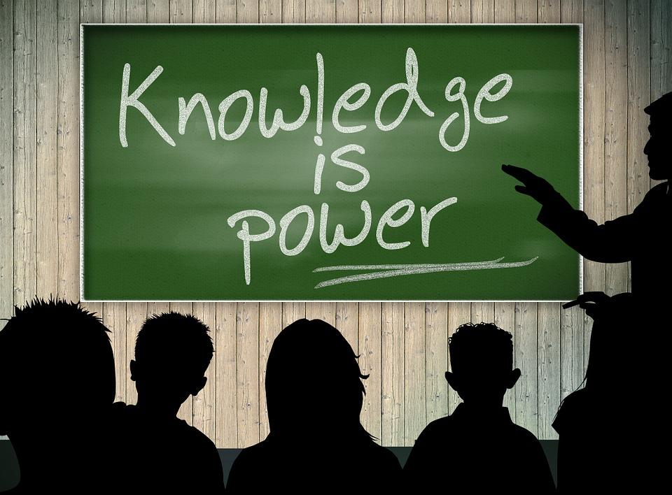 Des personnes regardent un tableau où c'est écrit : Knowledge is Power